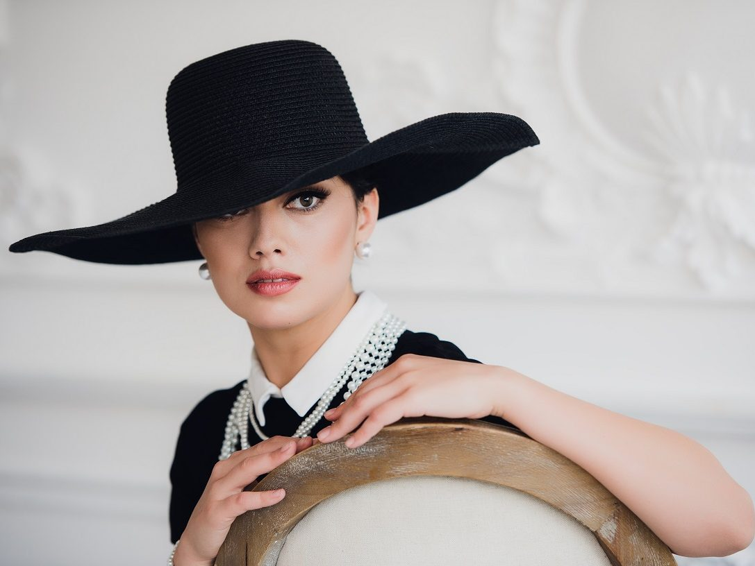 Elegant woman in black dress with a hat sitting on chair